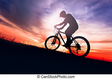 Silhouette of a biker on bike with sky background on sunset