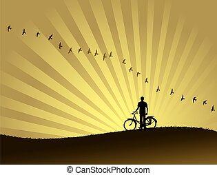 Silhouette of a biker watching a beautiful sunset