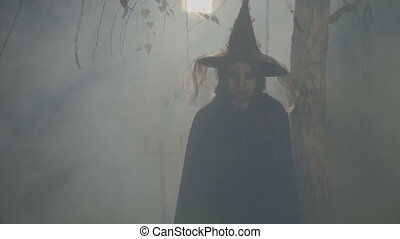 Silhouette of a black female witch playing with her hat on...