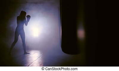 silhouette of a Boxer striking in smoke