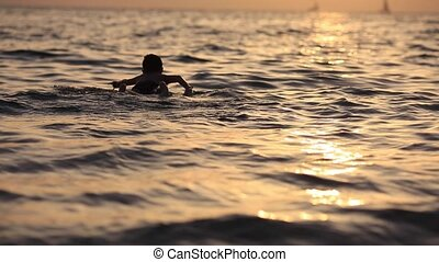 boy floating on the sea with a surfboard on the excellent...