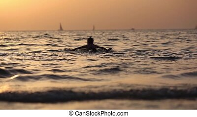 Silhouette of a boy floating on the sea with surfboard on...