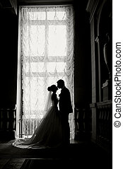 Silhouette of a bride and groom on the background of a window