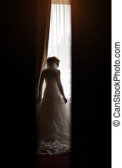 silhouette of a bride at the window