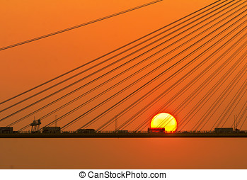 Silhouette of a bridge under setting sun