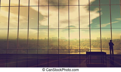 Silhouette of a businessman against the huge office window