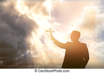 Silhouette of a businessman holding Christian cross