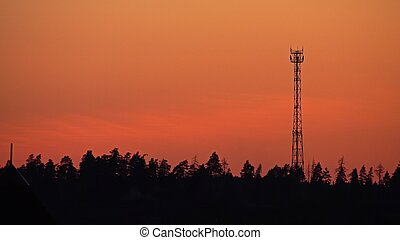 Silhouette of a cell tower against orange sunset sky