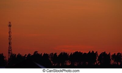Silhouette of a cellular tower or cell site against orange...