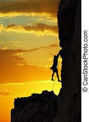 Silhouette of a climber over beautiful sunset - Man rock...