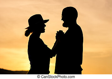 Silhouette of a couple holding hands at golden hour