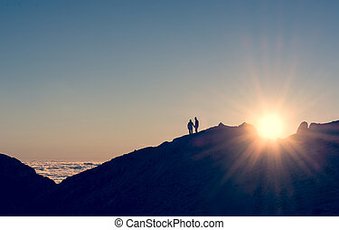 silhouette of a couple holding hands on a mountain ridge...