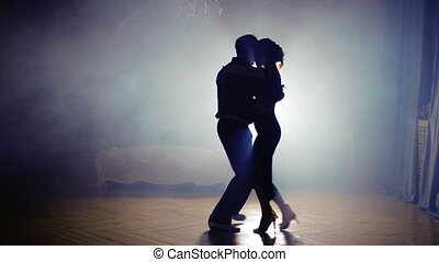silhouette of a couple in the fog of dancing tango -...