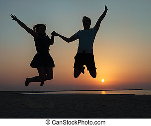 Silhouette of a couple - man and woman jumping on the beach