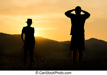 Silhouette of a couple watching sunset on the hill
