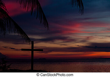 Silhouette of a Cross in front the sea at Sunset