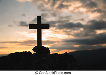 Silhouette of a cross on the mountain at sunset, hope concept.