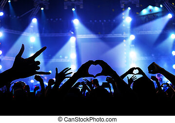 Silhouette of a crowd of cheering fans during a live concert, live music concert