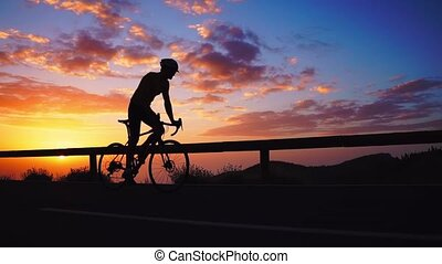 Silhouette of a cyclist at sunset in the mountains
