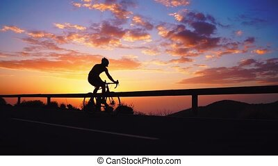 Silhouette of a cyclist at sunset in the mountains.