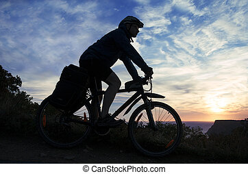 Silhouette of a cyclist on the background of the cloudy sky at sunset
