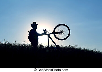 silhouette of a cyclist with a bike in the sun
