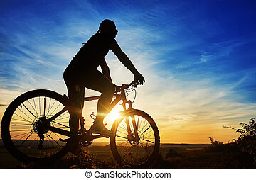 Silhouette of a cyclist with a bike on sky background on...