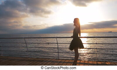Silhouette of a dancing ballerina in black ballet tutu and pointe on embankment above ocean or sea beach at sunrise or sunset. Young lady with long hair practicing stretching. SLOW MOTION.