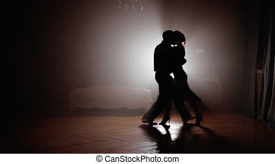 Silhouette of a dancing couple - Couple dancing tango in the...