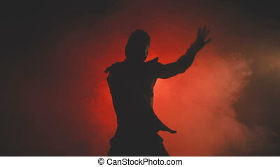Silhouette of a dancing man in mask