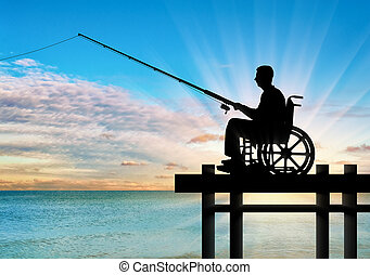 Silhouette of a disabled man in a wheelchair with a fishing rod in his hand fishing near the water on the pier