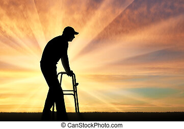 Silhouette of a disabled man walking, using a walker for the disabled
