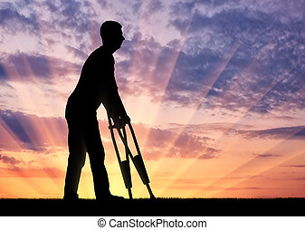 Silhouette of a disabled man with crutches walking against the sunset