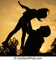 silhouette of a father and daughter who play outdoors at sunset background