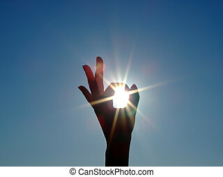 Silhouette of a female hand, the blue sky and the bright sun