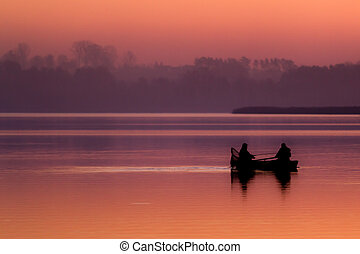 Silhouette of a fisherman catching fish in the boat at sunset
