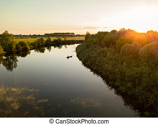 Silhouette of a fisherman in a boat on a river at sunset