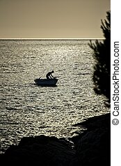 Silhouette of a fisherman in boat