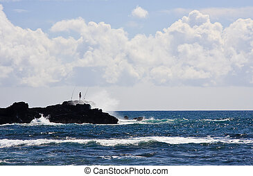 Silhouette of a fisherman on rocky headland off the coast of...