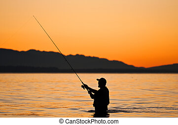 Silhouette of a fisherman with a fishing pole at sunset. - ...