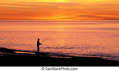 Silhouette of a Fisherman with a Fishing Rod at Sunset over the Sea