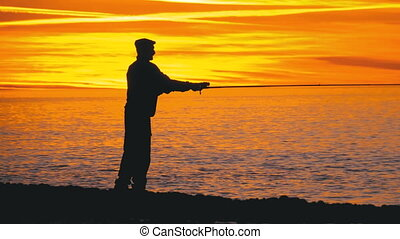 Silhouette of a Fisherman with a Fishing Rod at Sunset over...