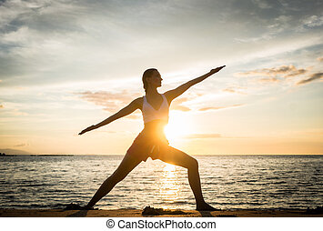 Silhouette of a fit woman practicing the warrior yoga pose again