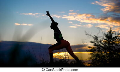 Silhouette of a fitness woman profile stretching at sunrise with the sun in the background