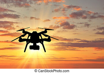 Silhouette Of A Flying Drone On Sunset Background