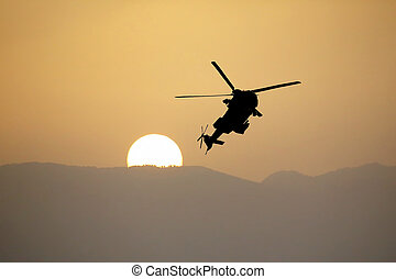 Silhouette of a flying helicopter against the setting sun