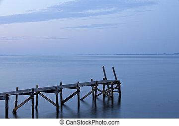 silhouette of a footbridge at the sea