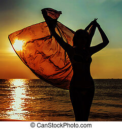 silhouette of a girl against the sunset sea