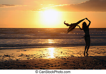 Silhouette of a girl at sunset on the beach of the Atlantic coast