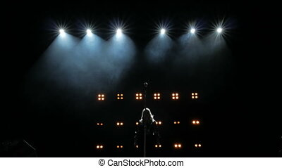 Silhouette of a girl comes to the microphone on the stage against a background of bright yellow lights